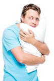 Vertical portrait of a man with a soft pillow on a white Stock Photos