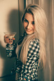 Vertical portrait of sexy blonde woman with glass of martini at Stock Photography