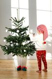 Vertical portrait of small blonde female child standes bare foot on wooden floor, decorates New Year tree, wears Santa s. Hat, likes preparation for holidays Royalty Free Stock Photos