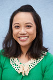 Vertical portrait of smiling Asian woman against grey wall Royalty Free Stock Photos