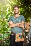 Vertical portrait of young attractive bearded dark-skinned farmer in blue t-shirt with garden tools holding hands Royalty Free Stock Photos