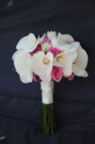 Vertical position of a bride bouquet with white orchids and pink roses. A beautiful bridal arrangement positioned against a dark background with flowers like stock photo