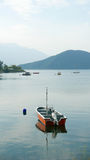 Vertical red fishing boat on peaceful lake Stock Photography