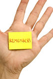 Vertical REMEMBER Note. Close up shot of a male hand with REMEMBER sticky note in palm Stock Images