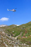 Vertical replenishment with flying helicopter and mountain panorama, Hohe Tauern Alps, Austria Stock Images