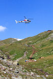 Vertical replenishment with flying helicopter and mountain panorama, Hohe Tauern Alps, Austria Royalty Free Stock Image