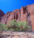Vertical Rock Face - Uluru. A sheer vertical rock face showing water channels on the surface of Australia's famous monolith, Uluru (Ayers Rock). Uluru – Kata Stock Photography