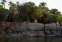 Typical white houses of a Nubian village surrounded by palm trees near Cairo Egypt and on the banks. Vertical rocky banks of the Nile river in Egypt with the Stock Photo