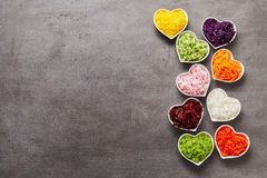 Vertical row of heart-shaped bowls of vegetables. Vertical row of colorful heart-shaped bowls of grated vegetables and lots of grey metal surface for copy space Stock Photo