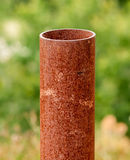 Vertical rusted metal pipe on green Royalty Free Stock Photo