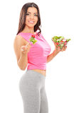 Vertical shot of an attractive woman eating a salad. Isolated on white background Royalty Free Stock Photos