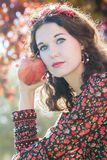 Vertical shot of autumn girl in fall wreath with big ripe apple fruit. In her arm Royalty Free Stock Photos