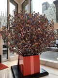 Vertical shot of a beautiful sculpture with many butterflies on the branches in a vase
