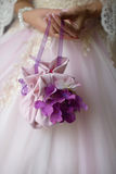 Close up of bride holding mini wedding bag with purple floral details. Vertical shot of bride dressed up in tulle dress with purple accents, holding delicate Royalty Free Stock Image