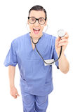 Vertical shot of a cheerful young doctor holding a stethoscope Royalty Free Stock Photos