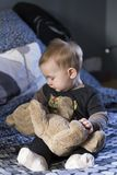 Vertical shot of cute fair baby girl sitting on bed looking at large vintage teddy bear stock photos