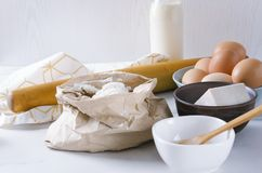 Ingredients for kneading the dough.Flour in the paper bag, eggs, dry yeast, milk.Kitchen utensils and components for dough. Vertical shot.Different components royalty free stock photo