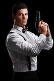Vertical shot of an elegant man holding a gun Royalty Free Stock Images