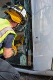 Vertical Shot of Emergency Responder Sawing Through Window on Mini Van