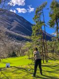 Vertical shot of a female playing golf in the green field with mountains in the background