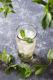Glass of mint julep served on the napkin.Grey bar table against gray wall.Empty space for your design royalty free stock photo