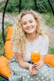 Vertical shot of good looking pretty young blonde female with curly hair, positive smile, spends free time with friends, have part royalty free stock image