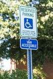 Reserved Parking for Handicapped Sign. Vertical shot of a handicapped parking sign with a 15 mile per hour sign below it.  Out of focus trees and a building in Royalty Free Stock Photos