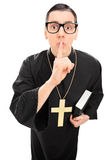 Vertical shot of a male priest holding finger on lips Royalty Free Stock Photo