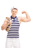 Vertical shot of a male sailor showing his bicep. Vertical shot of a male sailor carrying a rope around his shoulder and showing his bicep isolated on white Stock Images