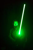Vertical shot of a male warrior with green laser sword royalty free stock photo