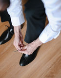 Vertical shot of a man tying shoelaces Royalty Free Stock Photography