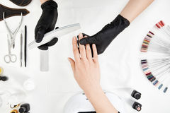 Vertical shot of manicurist filing nails with nail file. Royalty Free Stock Photos