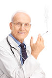Vertical shot of a mature doctor smoking cigarette Stock Image
