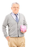Vertical shot of a mature man holding a piggybank. Isolated on white background Stock Photos
