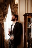 Vertical shot of pleased bearded young businessman wears black formal suit holds glass and drinks beverage, stands in stock images