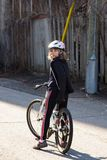 Vertical shot of pretty little girl with dark blond windswept hair sitting on her bicycle. In sunny alley looking back royalty free stock images
