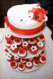 Vertical shot of a red and white wedding cake with small cupcake Stock Images