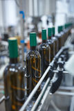 Vertical shot of a row of glass wine bottles moving by conveyor Stock Image