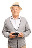 Vertical shot of a senior gentleman holding a camera Royalty Free Stock Photography