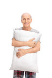 Vertical shot of a senior man holding a pillow Royalty Free Stock Photo