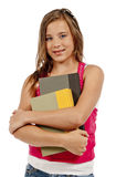 Girl Smiling Holding Books Isolated. Vertical shot of a teenage girl with braces holding her books and smiling at the camera.  White background.  Studio shot Royalty Free Stock Photography