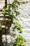 Vertical shot of wedding decorations with glass jars and white flowers hanging from poles
