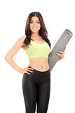 Vertical shot of a woman holding an exercise mat Royalty Free Stock Image