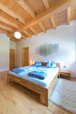 Vertical shot of wooden bed in bedroom Royalty Free Stock Image