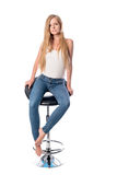 Vertical shot of a young beautiful long haired woman seating on an office or bar chair isolated on white background. Royalty Free Stock Photography