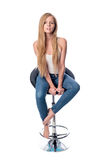 Vertical shot of a young beautiful long haired woman seating on an office or bar chair isolated on white background. Stock Photos