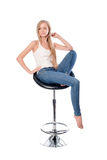 Vertical shot of a young beautiful long haired woman seating on an office or bar chair isolated on white background. Royalty Free Stock Image