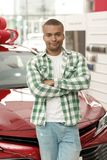 Handsome African man choosing new car at dealership stock photo