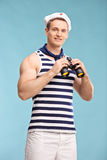 Vertical shot of a young male sailor holding binoculars Stock Photography