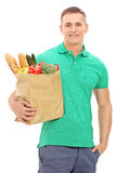 Vertical shot of a young man holding a grocery bag. Isolated on white background Royalty Free Stock Images